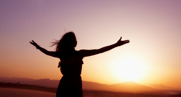 Woman with arms wide and a sunset